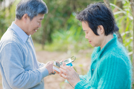 old couple use phone in the park Stock Photo