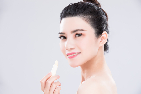 woman use lip balm on the gray background Stock Photo