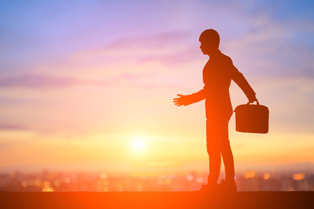 Silhouette of business man walk with sunset Stock Photo