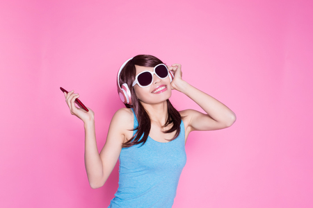 woman use phone listen music on the pink background Archivio Fotografico