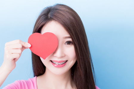 woman wear brace and take heart on the blue background 免版税图像 - 98386830