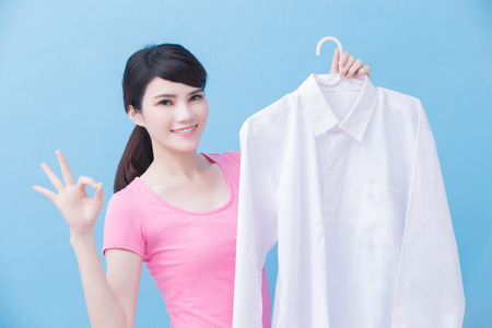 house take clean shirt and show ok to you on the blue background Stock Photo
