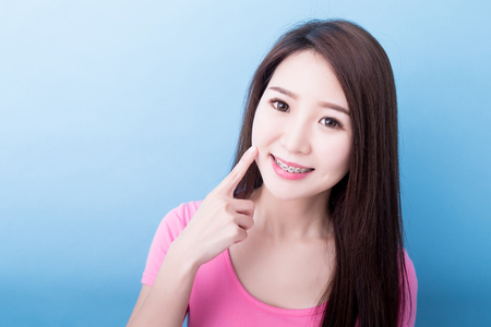 woman wear brace look you and smile happily on the blue background