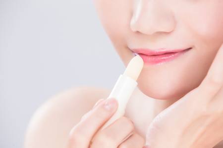 woman use lip balm on the gray background Imagens