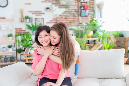 daughter give her mother hug and smile happily at home