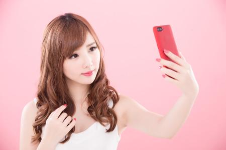 belleza mujer selfie en el fondo rosa