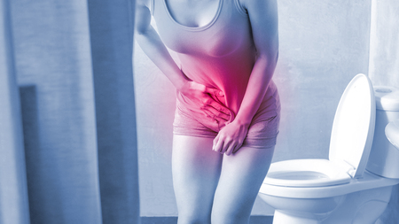 woman with urine urgency in the toilet Stock Photo