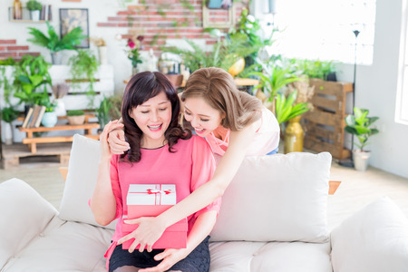 daughter give her mother gift and smile happily at home