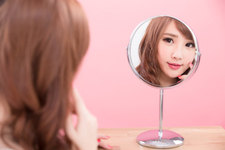 beauty makeup woman smile and look mirror on the pink background