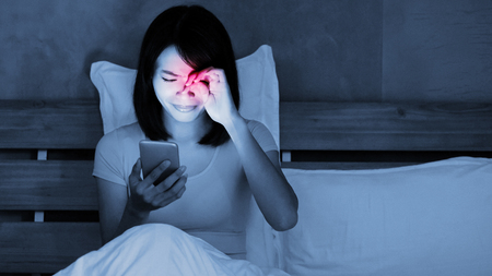 woman use phone with eye problem on the bed at night 免版税图像