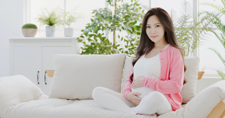 beauty pregnant women sit on sofa at home