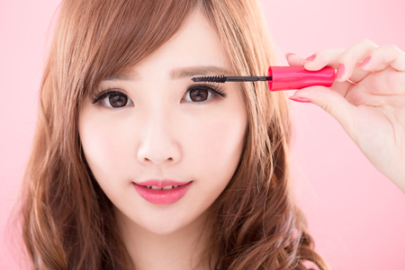 beauty woman take mascara on the pink background 写真素材