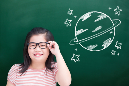 cute girl smile happily with earth on green chalkboard