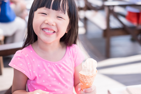 cute girl eat ice cream and smile happily