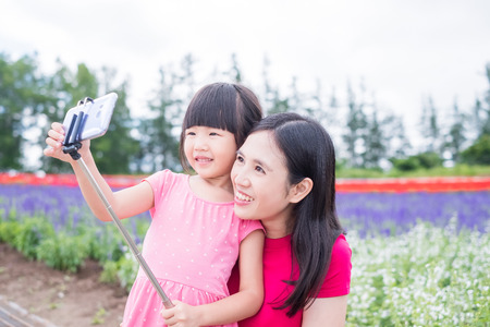 mother and daughter selfie and smile happily with beautiful landscape in Shikisai-no-oka Stock Photo