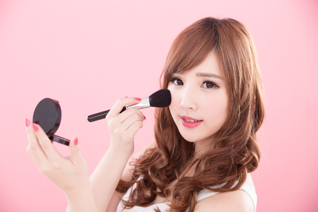 beauty woman take makeup brush on the pink background