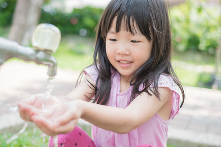 cute girl smile happily and wash hand