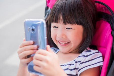 cute girl smile happily and use phone