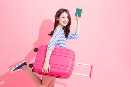 Frau nehmen Gepäckkoffer und Reisepass mit Reisekonzept Standard-Bild
