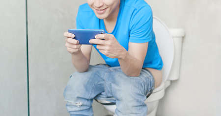 man take phone and smile happily in the toilet