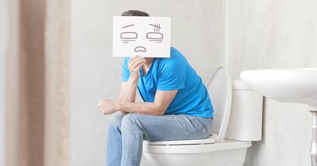 man verwarren bord met obstipatie in het toilet