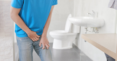 man with urine urgency in the toilet 스톡 콘텐츠