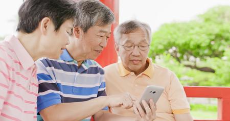 oude mensen zitten in paviljoen en gebruiken de telefoon met plezier Stockfoto