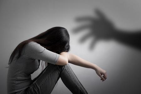 La donna depressione si siede sul pavimento con il concetto di molestie