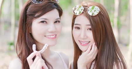 two beauty women wear brace and smile happily Stock Photo