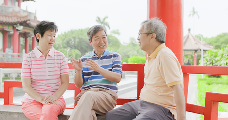 old people sit in pavilion and chatting happily 免版税图像