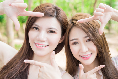 two beauty woman smile happily with brace and making frame gesture
