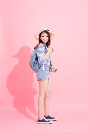 reisvrouw neemt camera en glimlacht gelukkig op de roze achtergrond Stockfoto