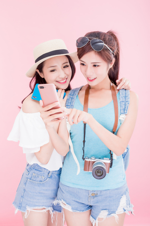 two travel woman smile happily and use phone on the pink bakcground 版權商用圖片