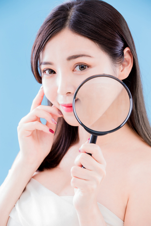 beauty skincare woman smile happily and take magnifying on the blue background Stock Photo