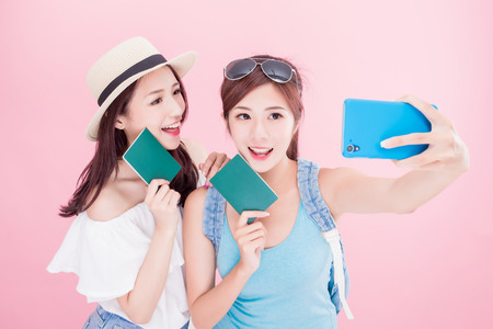 two beauty woman selfie happily with travel concept on the pink background Foto de archivo