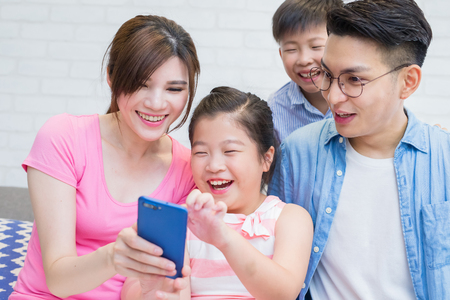 family sit on sofa and use phone happily at home