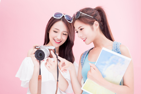 two travel woman take map and look picture in camera on the pink background