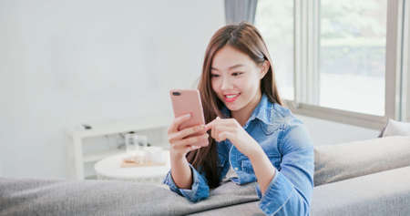 woman sit on sofa and use phone happily at home Banque d'images