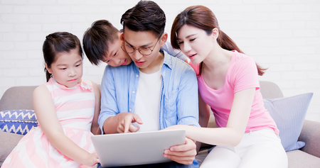 Happily family sit on sofa and use notebook at home Standard-Bild