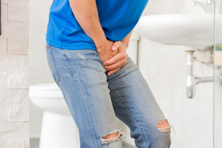man with urine urgency in the toilet Stockfoto