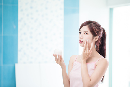 beauty woman with moisturizer concept in the bathroom 免版税图像