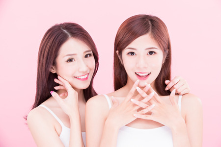 two beauty skincare women with health tooth on the pink background Foto de archivo