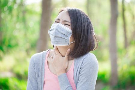 la donna indossa una maschera e sente mal di gola Archivio Fotografico