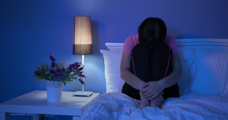 woman feel depression and sit on bed at home