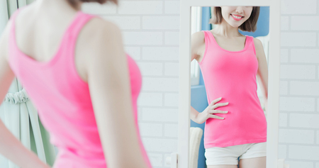 woman look mirror and show her slim waist to you