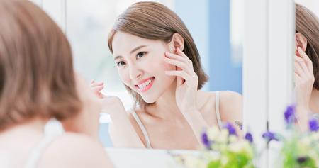 Schönheit Frau sehen Spiegel glücklich und berühren ihr Auge Standard-Bild