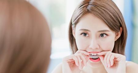 schoonheid vrouw kijkt spiegel glimlach gelukkig en neemt onzichtbare beugel