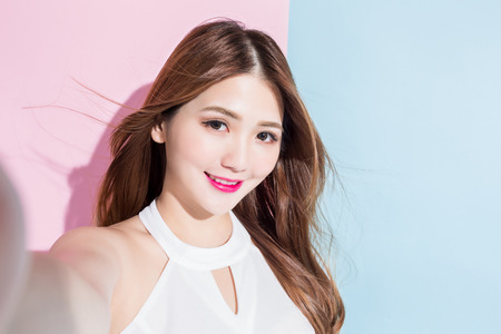 Photo en gros plan d'une jolie fille faisant selfie photo sur smar tphone isolé sur fond rose et bleu. Banque d'images