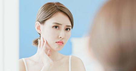 vrouw kijkt mirrior, voelt zich boos en raakt haar gezicht aan met een acneprobleem