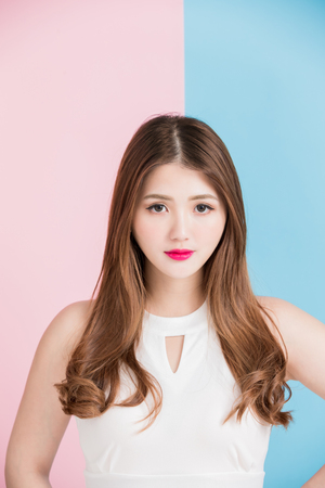 A pretty girl  dressed in white dress  standing with arms akimbo isolated on pink and blue background.
